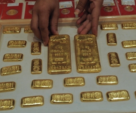 An Indian saleswoman arranges gold bars